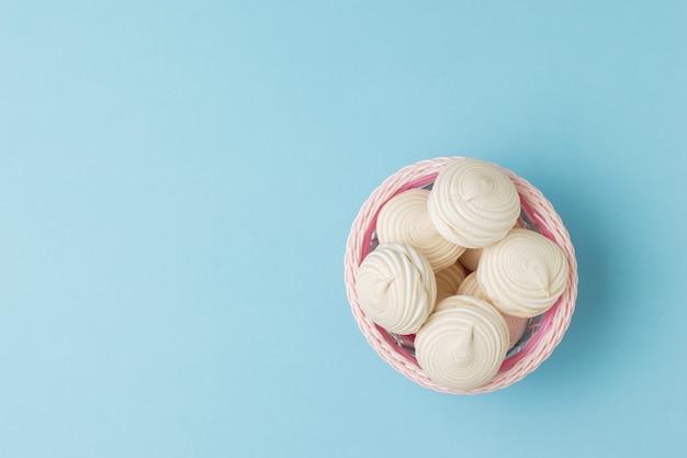 Vue de dessus d'un panier de meringue fraîche sur un bleu. délicieuse douceur des œufs et du sucre.