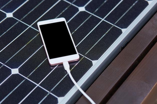 Vue de dessus d'un panneau d'énergie solaire installé sur un banc en bois, produisant de l'énergie, le smartphone étant sur la surface du panneau en train de se charger via un câble usb, en utilisant une autre source d'électricité. concept d'environnement.