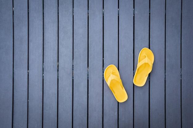 Vue de dessus de pantoufles jaunes sur le plancher de lattes de bois foncé