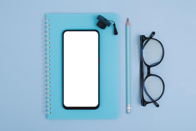 Vue de dessus de la papeterie, des lunettes avec téléphone et casquette diplômée sur une surface bleue