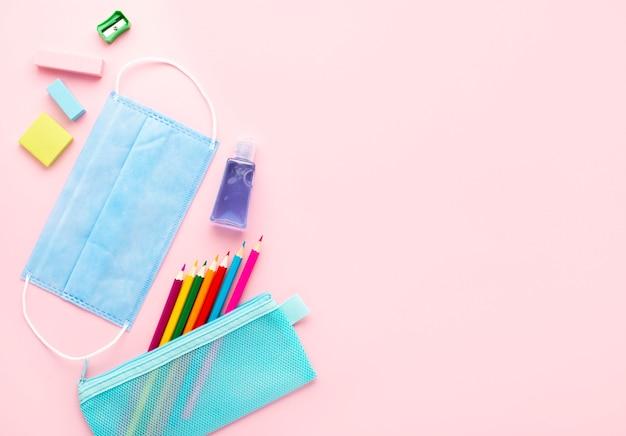 Vue de dessus de la papeterie de retour à l'école avec masque médical et crayons colorés
