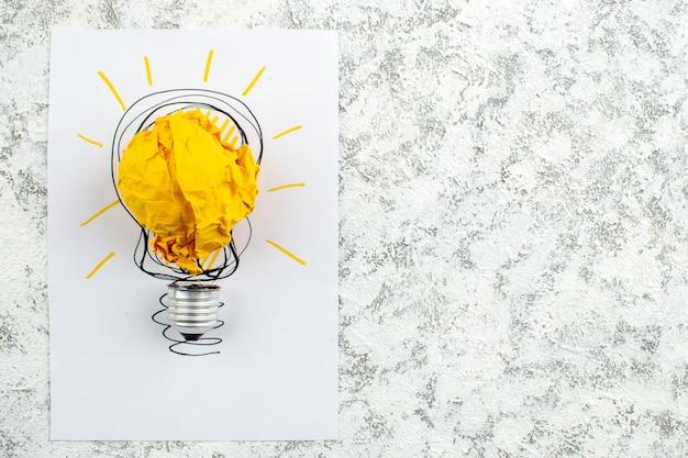 Vue de dessus papier froissé avec concept d'ampoule idée sur papier sur fond gris avec espace libre