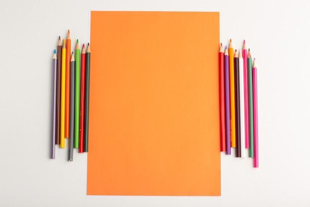 Vue de dessus papier orange vierge avec des crayons colorés sur une surface blanche