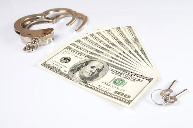 Vue de dessus d'un paquet de billets de cent dollars et de menottes et de clés pour eux se trouvent sur un tableau blanc. concept de crime sur la base du financement et de la dépendance au bien-être financier