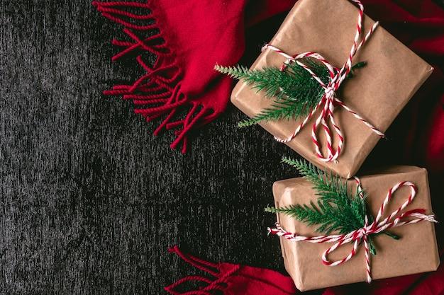 Vue de dessus des paquets de cadeaux emballés dans du papier brun et une écharpe rouge sur fond noir.