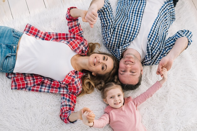 Vue de dessus des parents souriants avec leur fille allongée sur un tapis doux blanc