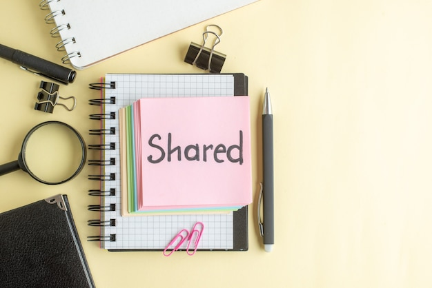 Vue de dessus partagée note écrite avec de petites notes de papier coloré sur fond clair bloc-notes emploi stylo école bureau business argent couleur travail cahier
