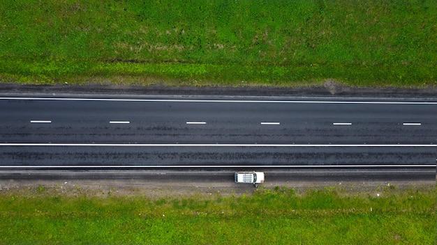 Vue de dessus. partie de l'autoroute au printemps. le long des champs verdoyants. sur un tronçon de route, une voiture est garée
