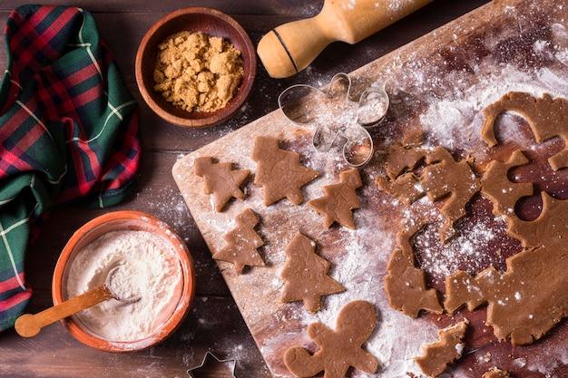Vue de dessus de la pâte à biscuits des arbres de noël avec rouleau à pâtisserie