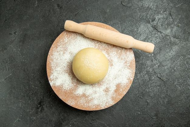 Vue de dessus de la pâte crue avec de la farine sur fond gris pâte farine repas cru alimentaire