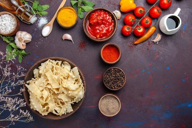 Vue de dessus de la pâte crue tranchée avec des tomates rouges et différents assaisonnements sur fond sombre pâte pâtes légume alimentaire
