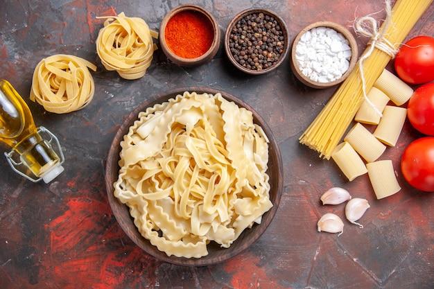 Vue de dessus de la pâte crue en tranches avec des assaisonnements sur la pâte à pâtes de surface sombre alimentaire sombre