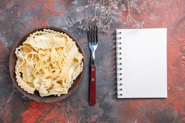 Vue de dessus de la pâte crue en tranches à l'intérieur de la plaque sur une surface sombre pâte foncée pâtes alimentaires crues