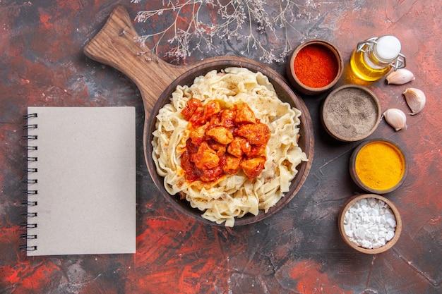 Vue de dessus de la pâte cuite avec du poulet et des assaisonnements sur une pâte de pâtes au sol sombre plat noir