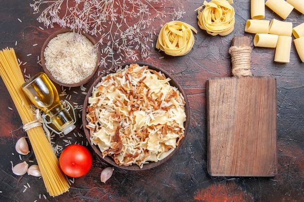 Vue de dessus de la pâte cuite en tranches avec du riz sur la pâte de plat de pâtes surface sombre foncé