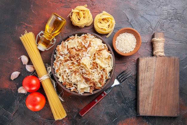 Vue de dessus de la pâte cuite en tranches avec du riz sur une surface sombre pâte de plat de pâtes foncées