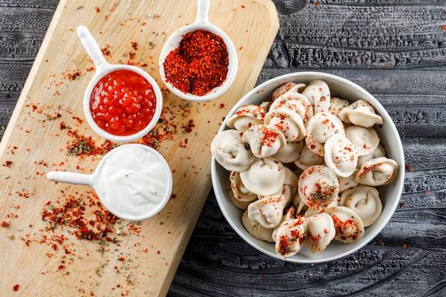Vue de dessus de la pâte dans un bol avec des épices rouges sur une planche à découper sur une surface en bois gris. horizontal