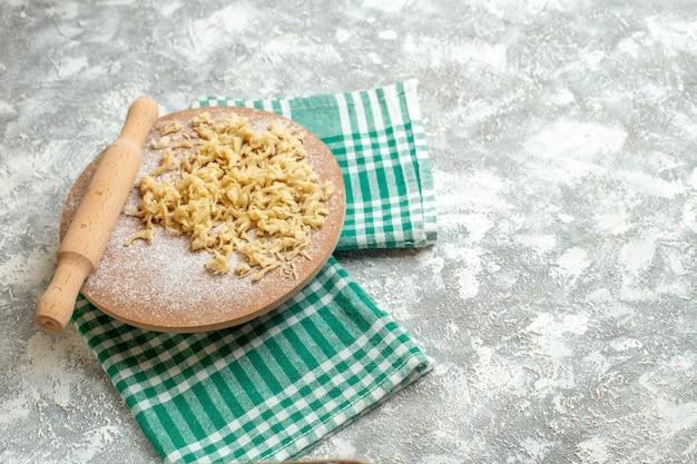 Vue de dessus de la pâte et du rouleau à pâtisserie sur un plateau de pâte sur une nappe sur fond gris