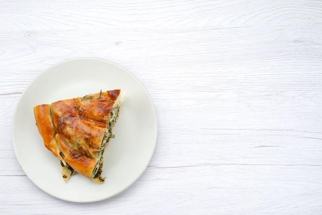 Vue de dessus de la pâte de légumes verts cuits en tranches à l'intérieur de la plaque blanche sur le fond blanc repas pâtisserie déjeuner verts