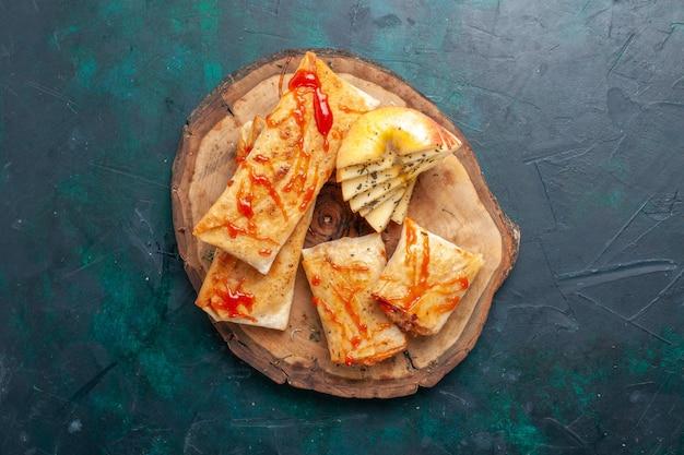 Vue de dessus de la pâte pita roulée en tranches avec garniture de viande et sauce sur un bureau bleu foncé