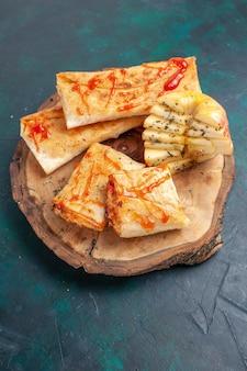 Vue de dessus de la pâte pita roulée en tranches avec sauce sur un bureau bleu foncé