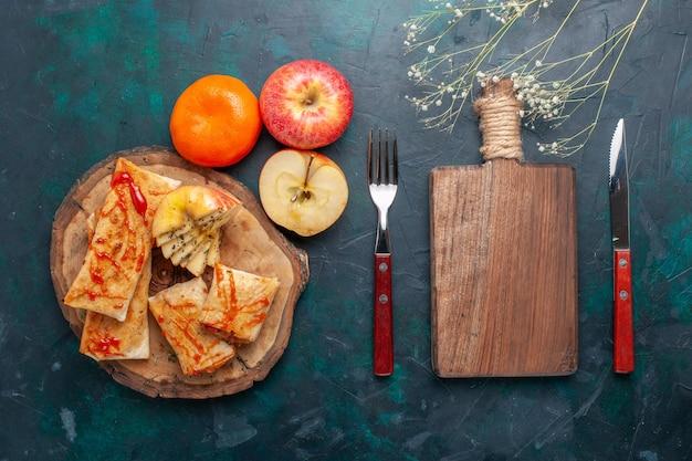 Vue de dessus de la pâte pita roulée en tranches avec sauce et fruits sur le bureau bleu foncé
