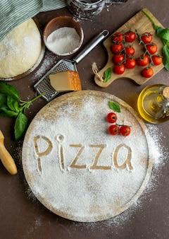 Vue de dessus de la pâte à pizza avec planche de bois et mot écrit en farine