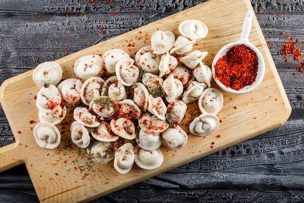 Vue de dessus de la pâte sur une planche à découper avec des épices rouges sur une surface en bois grise. horizontal