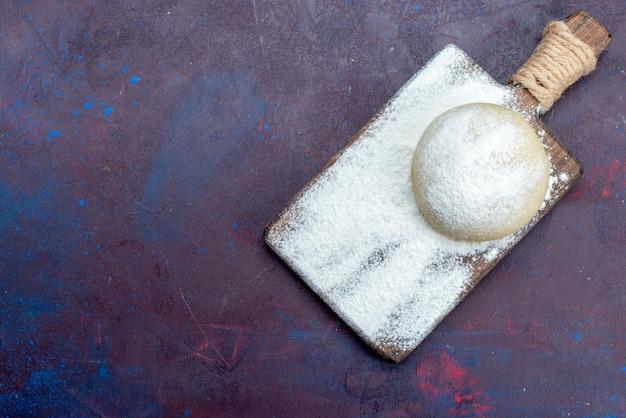 Vue de dessus de la pâte ronde avec de la farine blanche sur la surface sombre
