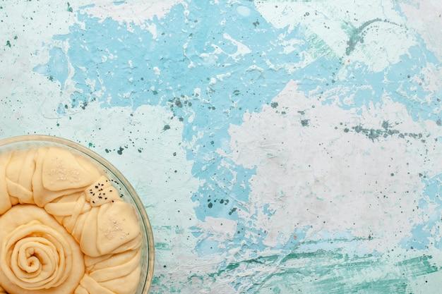 Vue de dessus de la pâte à tarte crue ronde formée sur la surface bleue
