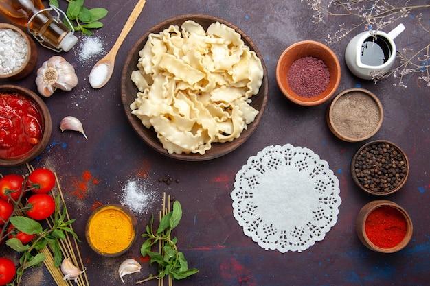 Vue de dessus de la pâte en tranches avec des assaisonnements et des tomates sur le dîner de pâtes alimentaires de pâte de repas de fond sombre