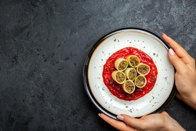 Vue de dessus de la pâte avec des tranches de viande en tranches avec sauce tomate sur espace gris