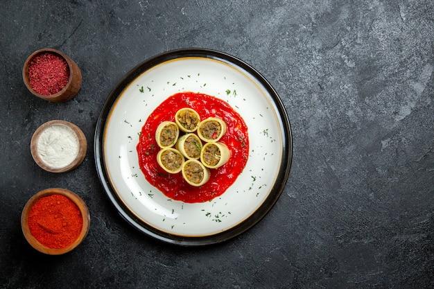 Vue de dessus de la pâte avec de la viande tranchée avec de la sauce tomate et des assaisonnements sur l'espace gris