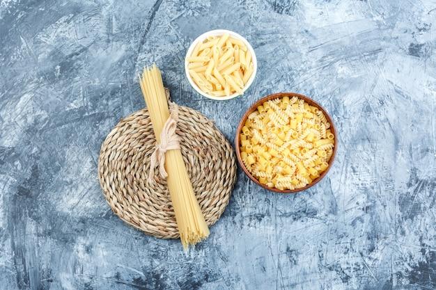 Vue de dessus des pâtes assorties dans des bols sur fond de plâtre et de napperon en osier gris. horizontal
