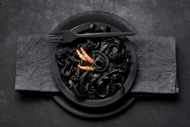 Vue de dessus des pâtes aux crevettes noires avec fourchette et serviette