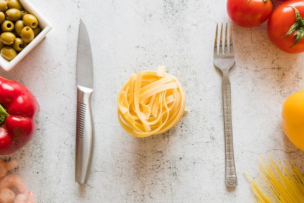 Vue de dessus des pâtes avec un couteau et une fourchette