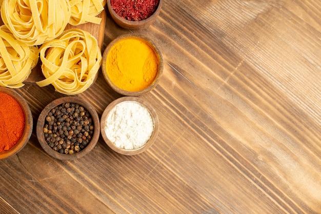 Vue de dessus pâtes crues conçues avec des assaisonnements sur un bureau en bois brun pâte alimentaire repas pâtes