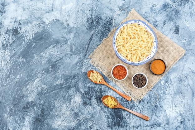 Vue de dessus des pâtes crues dans un bol et des cuillères en bois avec des épices sur du plâtre et un morceau de fond de sac. horizontal