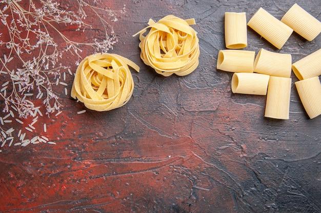 Vue de dessus des pâtes crues différentes formées sur une pâte de pâtes de couleur de surface foncée