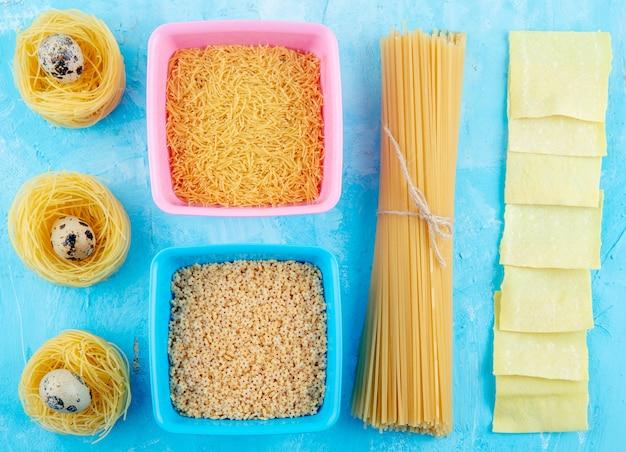 Vue de dessus des pâtes crues de différentes formes et types comme nid de pâtes spaghetti jaune avec de petits œufs petits vermicelles et pâtes en forme d'étoiles sur bleu