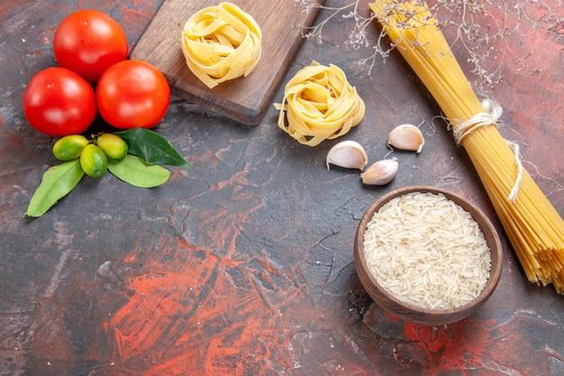 Vue de dessus des pâtes crues avec du riz et des tomates sur la pâte de pâtes de surface sombre crue