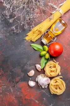 Vue de dessus des pâtes crues avec de l'huile et des tomates sur la surface sombre des pâtes à pâte crue