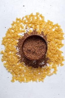 Vue de dessus des pâtes crues jaunes peu avec assiette de sarrasin sur le bureau blanc pâtes italie repas alimentaire