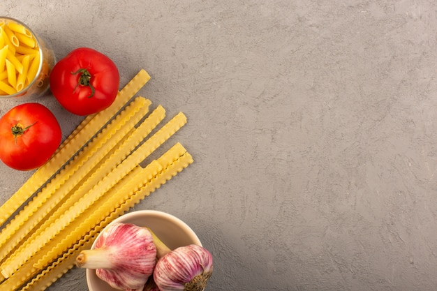 Une vue de dessus des pâtes crues jaunes sèches longues pâtes italiennes avec des tomates rouges et de l'ail isolé sur le fond gris repas alimentaire de légumes
