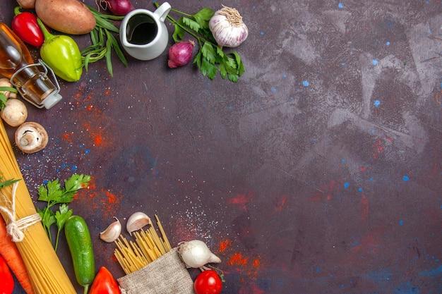 Vue de dessus des pâtes crues avec des légumes frais sur une salade de repas de bureau sombre
