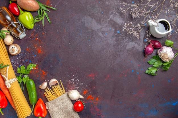 Vue de dessus des pâtes crues avec des légumes frais sur une surface sombre de la salade de repas