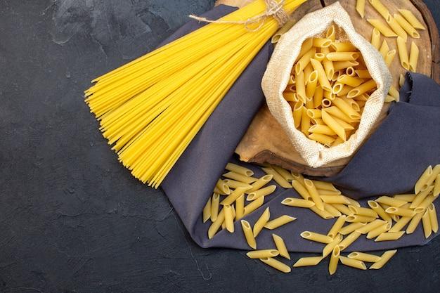 Vue de dessus pâtes crues longues et peu sur fond sombre nourriture pâtes dîner repas cuisine couleurs cuisine obscurité