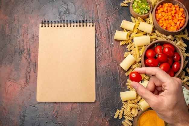 Vue de dessus pâtes crues penne rigatoni spirales légumes hachés et curcuma dans des bols tomate cerise dans un bloc-notes à main féminin sur une table en bois