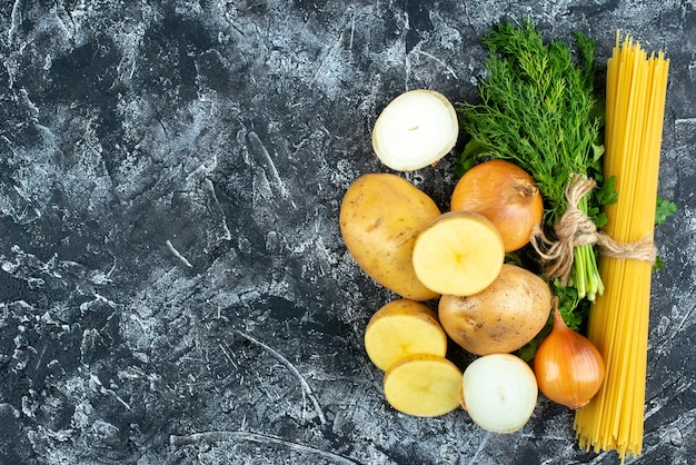 Vue de dessus des pâtes crues avec pommes de terre, persil et oignons sur une surface gris clair