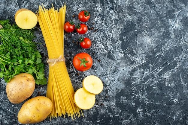 Vue de dessus des pâtes crues avec pommes de terre, persil et tomates sur une surface gris clair